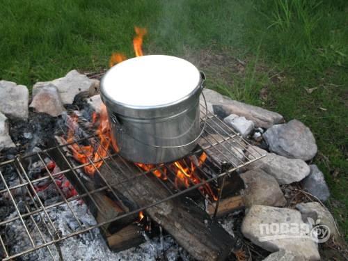 Поставьте котелок на огонь и доведите бульон до кипения.
