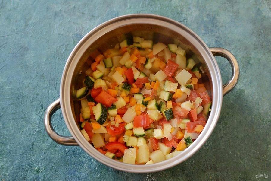 Убавьте температуру на минимум, добавьте картофель, сладкий перец, помидоры и цукини. Готовьте еще 10-15 минут, периодически помешивая.