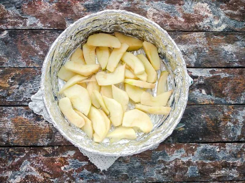 Возьмите форму для выпекания, смажьте ее растительным маслом, на дно выложите нарезанные яблоки.