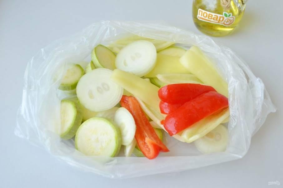 2. Кабачок нарежьте кружочками толщиной примерно 5-7 мм, такими же колечками нарежьте лук. У перца удалите семена, порежьте дольками. Сложите все овощи в пакет.