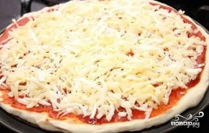 6.Смазываем блин кетчупом, после чего слоями выкладываем ингредиенты: сначала лук, потом шампиньоны, затем тертый сыр. Слегка перчим. Отправляем пиццу в разогретую духовку и запекаем 25 минут.