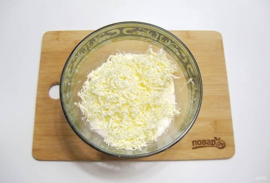 Натрите на терке холодное сливочное масло прямо в миску с мукой и сахаром.