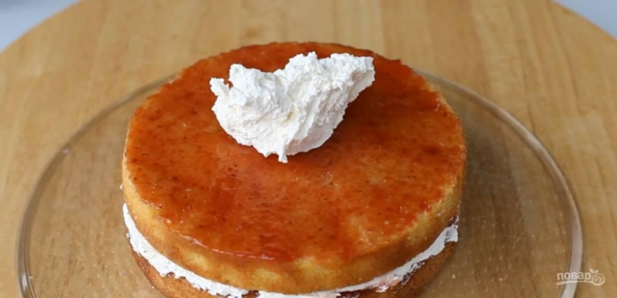 6.Наложите на первый бисквит — второй, проделайте ту же процедуру (смажьте клубничным джемом и белково-масляным кремом).