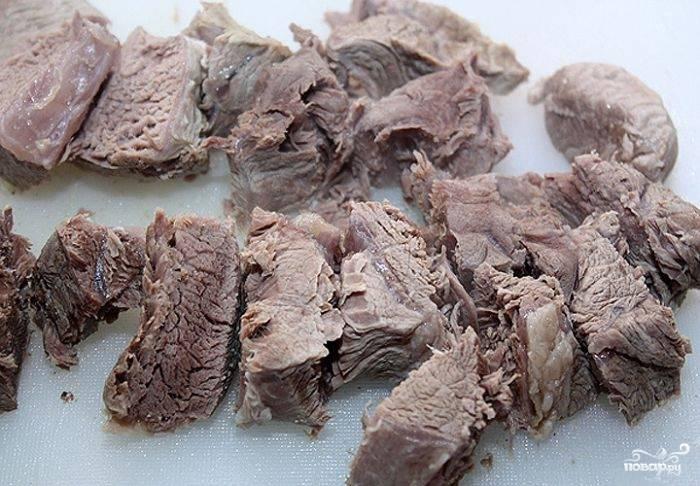 После того, как мясо сварится, достаем его из бульона, режем на маленькие части и откладываем в сторону.