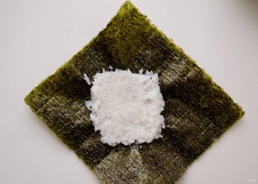 Лист нори положите гладкой стороной вниз, выложите на него большую ложку риса. Разровняйте рис и придайте ему форму квадрата.