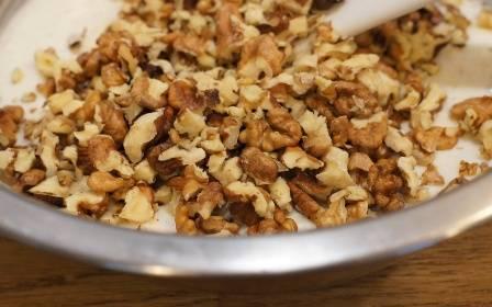 Очищенные грецкие орехи слегка измельчаем. Кусочки не должны быть мелкими, гораздо приятнее будет, если в печенье вам попадется крупный кусочек:) Отправляем орехи к полученной массе.