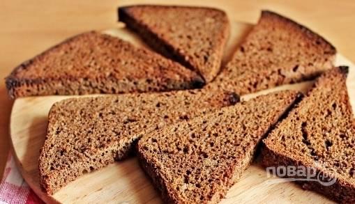 Ломтики черного хлеба подсушите в тостере или в духовке. Пока они готовятся, налейте в кастрюльку воду, положите в нее яйца и варите их десять минут вкрутую. Остудите яйца и очистите их от скорлупы.
