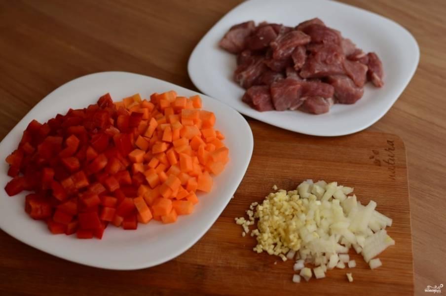 Мясо порежьте средними кусочками, можно кубиками. Лук измельчите кубиками, чеснок — произвольно. Морковку порежьте мелко.