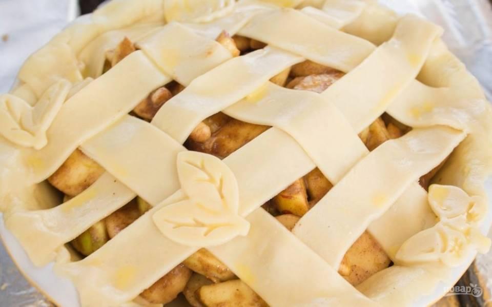 Затем на тесто выложите яблоки и груши. Сделайте полоски из теста. Закройте ими пирог, прижимая края. По желанию сделайте узор из теста. Взбейте яйцо с молоком, и промажьте этой смесью тесто.