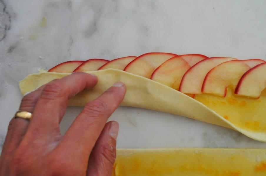 """Уложите на полоску теста яблоки. Яблоки стоит класть внахлест. Затем аккуратно """"накройте"""" яблоки нижней частью теста."""