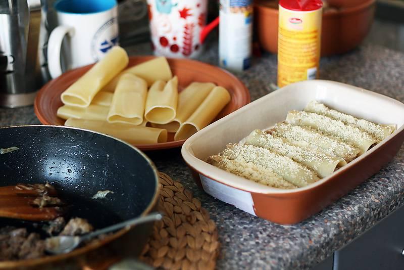 5. На дно формы для запекания вылейте около трети соуса. Остывшие трубочки наполните начинкой и выложите в форму. Присыпьте немного сыром и залейте оставшимся соусом. Отправьте форму в разогретую духовку минут на 10.