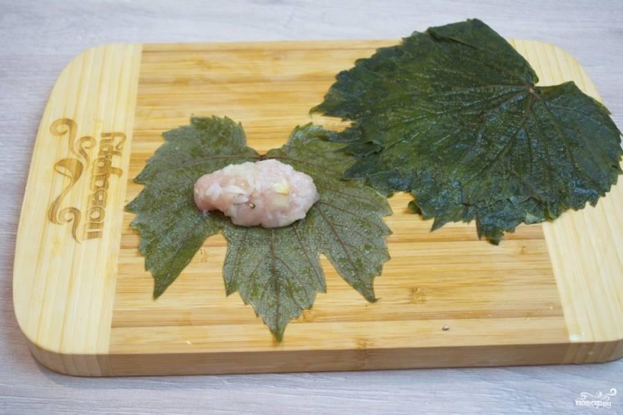 Для приготовления долмы в магазинах продают подготовленные листья. Я беру листики, заготовленные мною с лета. У меня мороженные листья винограда, без соли. Вымачивать их не нужно. Если ваши листья приготовлены в рассоле, их нужно предварительно вымочить, чтобы удалить лишнюю соль. На листик винограда (обрежьте ножку листика) выложите котлетку из подготовленного фарша.