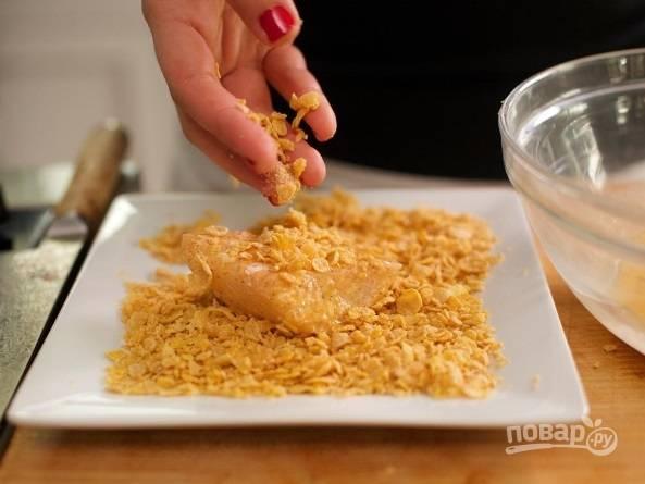 Теперь займитесь рыбой. В миске перемешайте хлопья с паприкой, солью и перцем. Филе обмакните в муке, потом в взбитых яйцах, и, наконец, в приготовленной панировке.