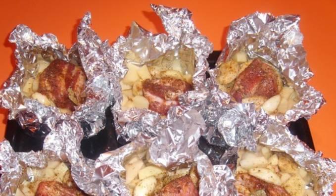 Разделите свинину на порционные кусочки и замаринуйте мясо в маринаде из растительного масла, соли и специй для шашлыка. Можно оставить мариноваться на ночь в холодильнике. Утром раскладываем кусочки свинины в фольгу, добавляем порезанный картофель и зубчики чеснока.