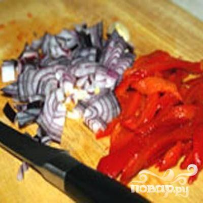 2.Очищаем и мелко нарезаем лук. Промываем перец, смазываем маслом и запекаем в духовке под гриль (температура 250 градусов), примерно 40 минут, изредка переворачиваем. С остывшего перца снимаем кожицу, разрезаем вдоль, семена удаляем. Нарезаем перец полосками. Говядину нарезаем кусочками.