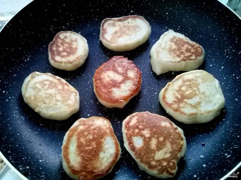 Поставьте сковороду на средний огонь, смажьте ее растительным маслом. Тесто не перемешивайте! Берите аккуратно столовой ложкой по стенке миски и выкладывайте на сковороду. Обжарьте оладьи с двух сторон до румяности.