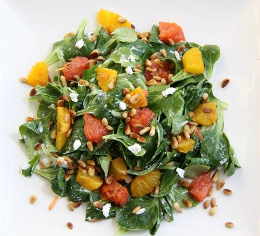 В эту же посуду, к салату и сыру добавьте орешки и цитрусовые, заправьте маслом. Тщательно все перемешайте.