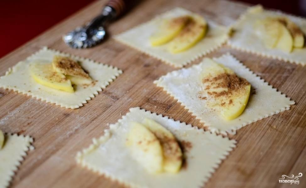 Вырежьте из слоенного теста квадратики. Яблоки очистите от кожуры и нарежьте небольшими дольками. Кладите по дольке (или несколько) в квадратик, сверху посыпьте корицей. По желанию можно использовать и другие ароматные специи.