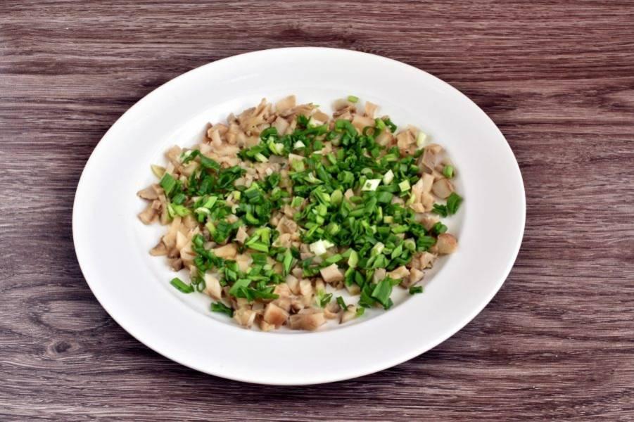 Салат выложите слоями на плоскую тарелку. Первым слоем мелко нарежьте соленые грибы и посыпьте их рубленым зеленым луком.