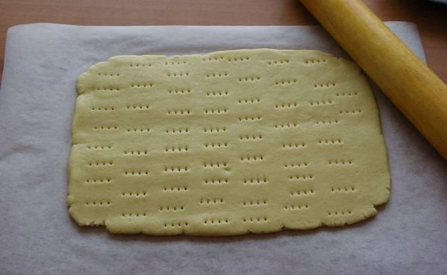 4. Ту, что побольше раскатать и выложить на противень, можно его предварительно застелить пергаментом, но тесто абсолютно не липнет. Сделать вилкой небольшие проколы и отправить тесто в разогретую духовку.