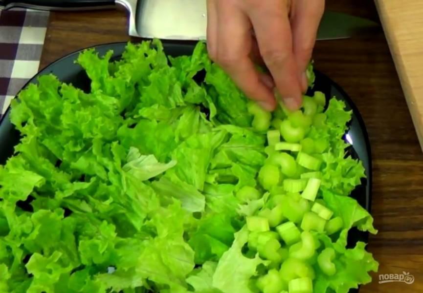 1. Дно блюда выстелите измельченными листьями салата. Нарежьте стебель сельдерея и выложите на листья салата (сельдерей можно заменить свежим огурцом).
