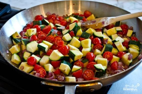 4. Выложите на сковороду кабачки и нарезанные помидоры. Тушите на среднем огне около 10 минут.