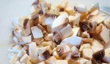 Пока картофель сварится, нарезаем грибы кубиками, лук и чеснок - измельчаем.