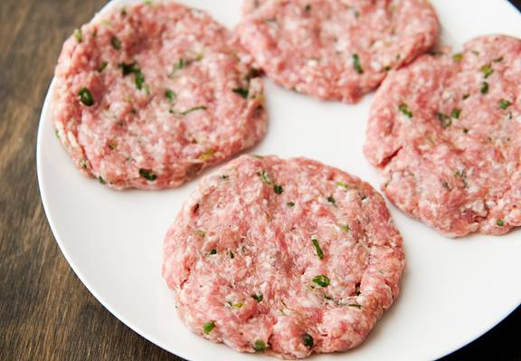 Фарш смешайте с зеленым луком, добавьте в него пару ложек рыбного соуса и сформируйте четыре одинаковых котлеты.