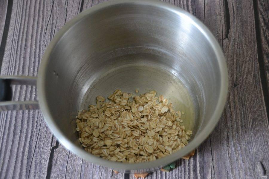 В сотейник с толстым дном положите топленое сливочное масло, всыпьте овсяные хлопья.
