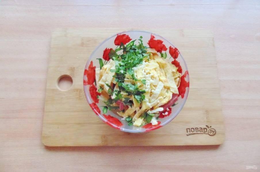 Мелко нарежьте петрушку и чеснок. Добавьте в салат.