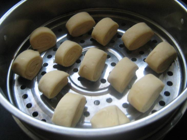 Круги пароварки или мантышницы смазываем растительным маслом. Рулеты разрезаем на кусочки и выкладываем на круги. Варим на пару минут 20-25.
