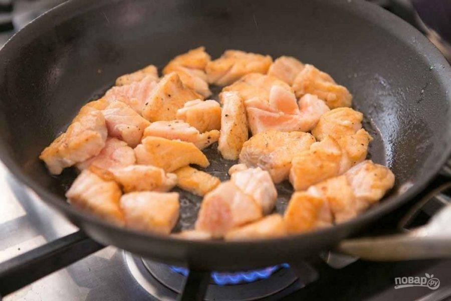 Лосось нарежьте некрупным кубиком, слегка присыпьте мукой и перцем. Растопите в сковороде сливочное масло и обжарьте рыбу до легкого золотистого оттенка.