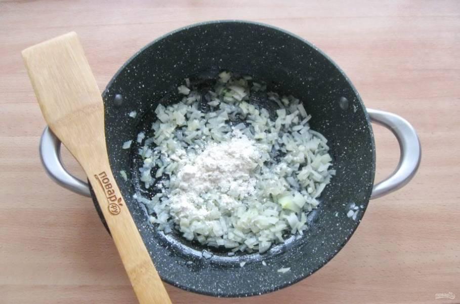 Приготовьте соус. Репчатый лук очистите, помойте и нарежьте. Выложите в сковороду. Налейте немного подсолнечного масла. Добавьте муку. Перемешайте и немного прогрейте в течение 3-4 минут.