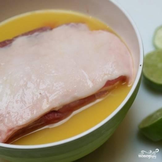 2. Кусок свинины выложите в миску с апельсиновым соком.