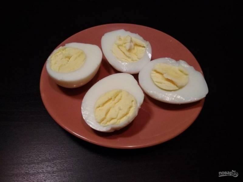 3. В это время яйца отварите вкрутую. Затем разрежьте их на половинки.