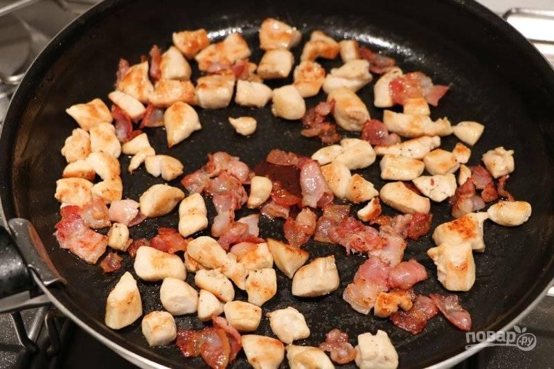 Филе промойте и нарежьте вместе с беконом небольшим кубиком. На разогретой сковороде обжарьте бекон до золотистого цвета в течении 5-7 минут. Добавьте филе и готовьте еще 5 минут.