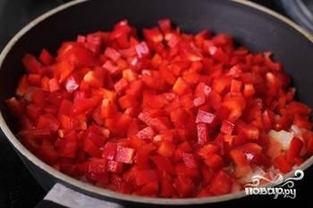Перцы помойте, удалите семена и плодоножки, затем нарежьте мелкими кубиками. Добавьте их на огонь и тушите ещё 10 минут.