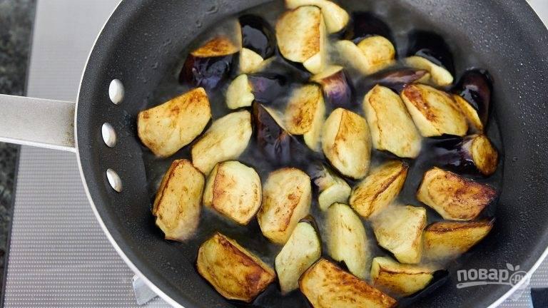 2.Баклажаны нарежьте кусочками около 2,5-3 см. Выложите баклажаны в сковороду и обжарьте их с каждой стороны до золотистой корочки, переложите на бумажное полотенце.