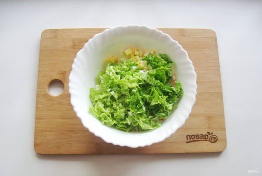 Пекинскую капусту нарежьте тонко. Добавьте в салатник.