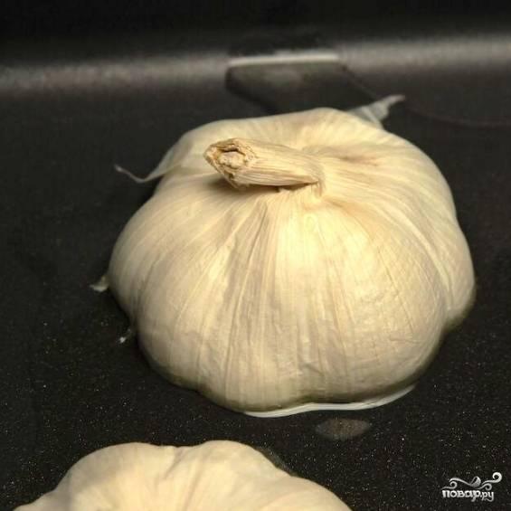 В форму для запекания наливаем оливковое масло, туда же надрезом вниз складываем головки чеснока.