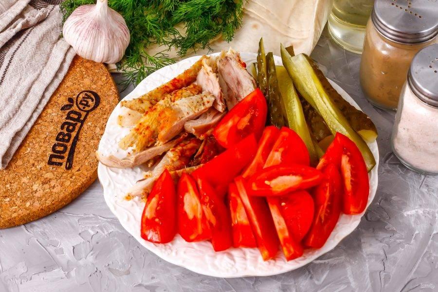 Срежьте мясо с обжаренных куриных голеней, нарежьте его полосками. Промойте помидоры и вырежьте зеленые сердцевинки. Нарежьте томаты ломтиками, а соленый огурец — брусочками. По желанию можно использовать свежий огурец.