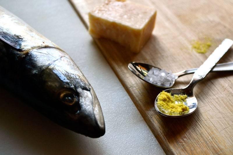 Нам понадобится всего несколько ингредиентов: скумбрия, сыр и специи. Разрезаем скумбрию пополам. Кладем на противень, смазанный растительным маслом.