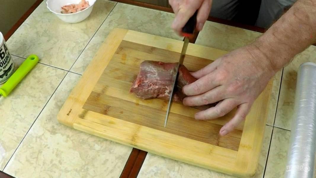 Отрезаем от куска нерабочей мышцы (вырезки) около 10 см мяса, смачиваем доску водой и накрываем пищевой плёнкой для отбивки.