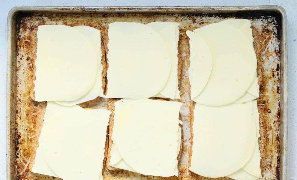 Нарежьте тонкими кусочками колбасный сыр. На противень выложите хлеб, затем колбасный сыр.