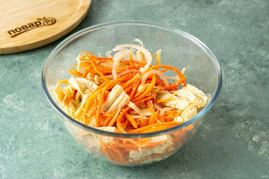 В глубокой миске соедините соевую спаржу, морковь и репчатый лук. Перемешайте.