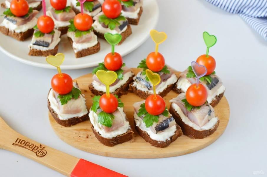 Далее украсьте листочком петрушки, на шпажку нанизайте помидор и вставьте в бутерброд.