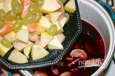 Сначала подготовьте фрукты с вином. Яблоко и грушу нарежьте небольшими кусочками. Мандарин очистите от кожуры и плёнок с косточками. Виноград промойте. Вино подогрейте в кастрюле. Затем выключите огонь и добавьте в вино все фрукты. Оставьте их в таком виде на 30 минут.