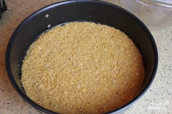 1. Печенье перетираем в крошку вместе с размягченным маслом. Укладываем плотным слоем на дно разъемной формы.