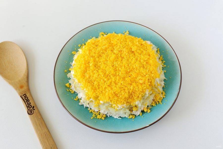 На картофель выложите тертые на мелкой терке желтки. Белки оставьте для украшения.