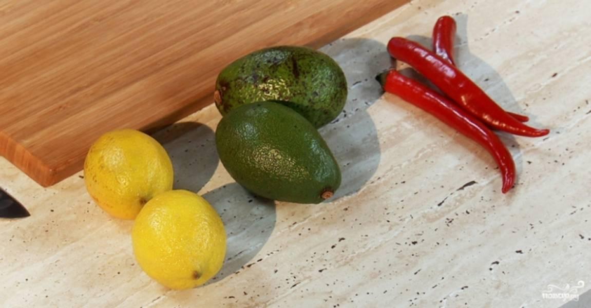 Приготовьте начинку. Авокадо помойте, почистите, мелко нарежьте. Перец чили помойте, удалите из него семечки, измельчите. Половину луковицы почистите и мелко нашинкуйте. Смешайте эти ингредиенты вместе с соком половины лимона, солью и растительным маслом.